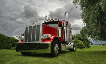 A red semi tractor truck on a green lawn with dramatic clouds in background.